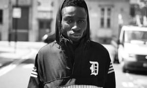 kojey radical standing in the street in a hooded top