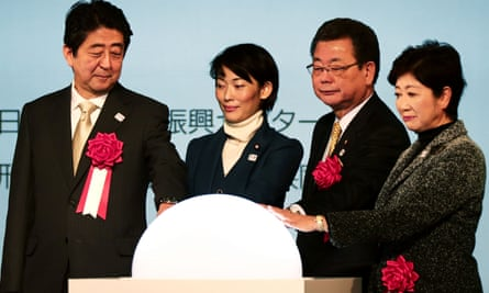 Shinzo Abe and other dignitaries launch construction of the stadium by putting their hands on a rotating globe.