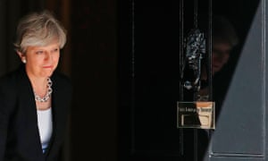 Theresa May exits the door of 10 Downing Street.