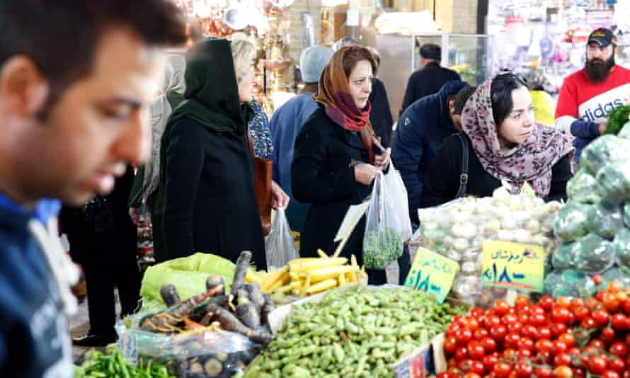 Iranians shop in a bazaar in Tehran as sanctions covering Iran's shipping, financial and energy sectors –waived as part of 2015 nuclear deal – took effect.
