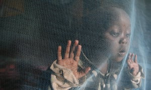 A small child plays under a insecticide treated mosquito net in the Kibera area of Nairobi, Kenya.