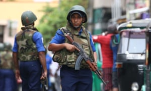 Sri Lankan soldiers stand guard as security personnel inspect the debris of a car after it explodes when police tried to defuse a bomb near St. Anthony's Shrine in Colombo.