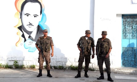 Tunisian soldiers stand guard outside a polling station in Tunis