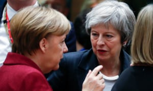 Angela Merkel, the German chancellor (left), speaking to Theresa May at the EU summit