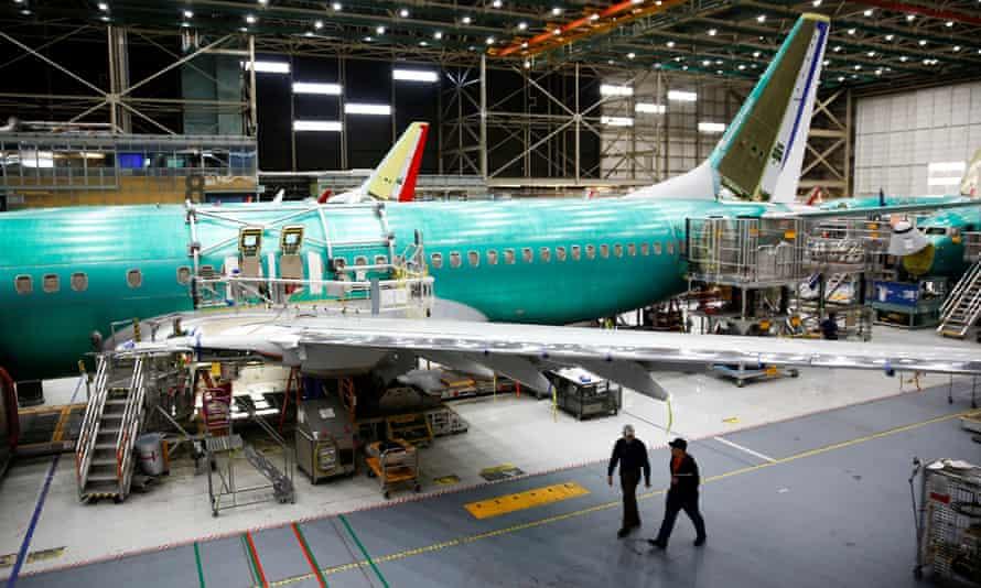 Two workers walk under the wing of a 737 Max aircraft at the Boeing factory in Washington
