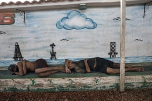 Fishermen nap in front of a mural of Lake Maracaibo