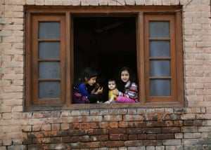 Children sit in the window of a house in Srinagar, India
