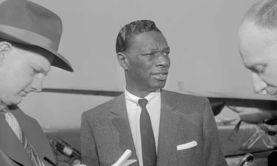 """Singer Nat """"King"""" Cole, who was assaulted during an engagement in Birmingham, Ala., is interviewed by newsmen as he stopped at Washington National Airport while en route to Raleigh, North Carolina, to resume his southern tour."""