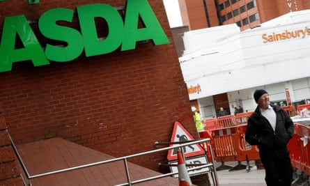 A man walks past branches of ASDA and Sainsbury's in Stockport