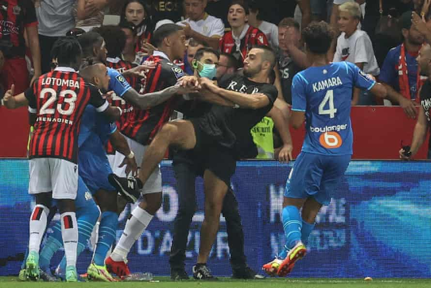 Fans and players fight on the side of the pitch at the Allianz Riviera in Nice.