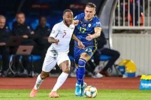 England forward Raheem Sterling tussles with Kosovo midfielder Benjamin Kololli.