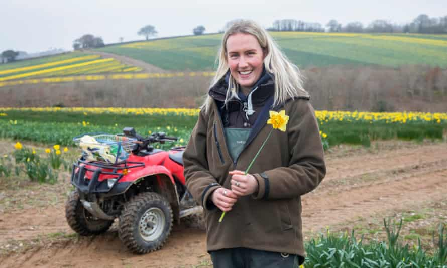 Frances Hosking standing next to a quad bike, smiling,  holding a single daffodil, with a backdrop of yellow-tinged fields behind her