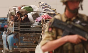 A British soldier stands guard as families flee Basra in Iraq in 2003.