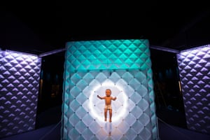 """A robotic baby lies on an illuminated """"mattress"""" at the entrance to the Science Museum's Robots exhibition. The nappy-wearing robot breathes, moves its arms and legs, and opens and closes its eyes."""