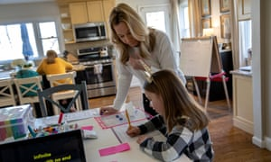 Farrah Eaton helps her two daughters, Elin, left, and Nola with home schooling.