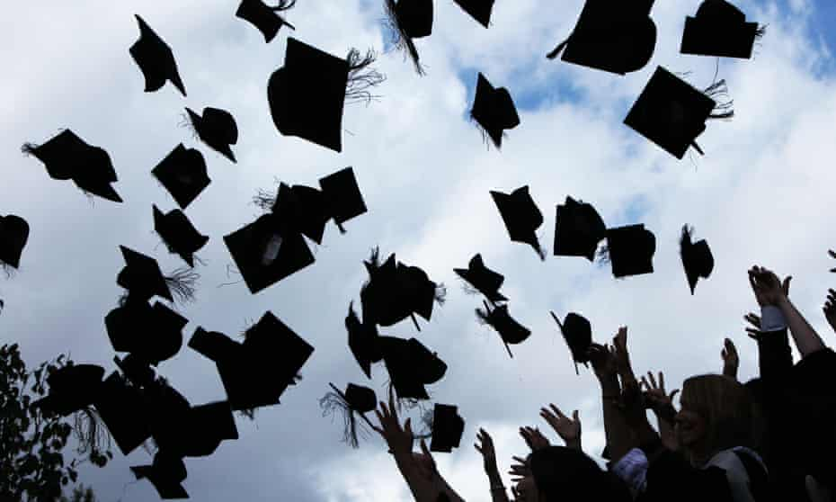 Students throw their mortarboards in the air after their graduation ceremony.