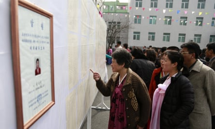 People inspect the list of voters next to a portrait of the only candidate in North Korea's legislature election.