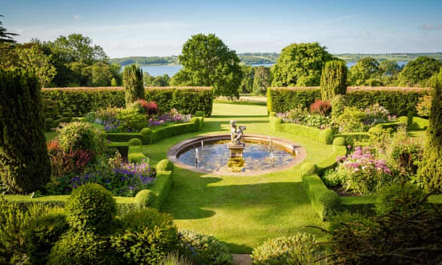 A landscaped garden set around a water feature at Hambleton Hall with Rutland Water in the distance.