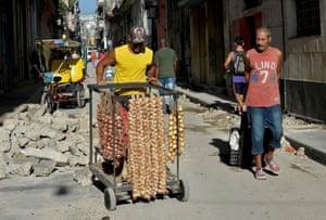 A vendor pushes a cart through the streets of Havana, Cuba