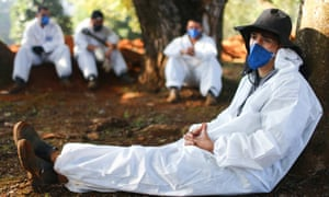 Cemetery workers in protective suits rest between burials at Vila Formosa cemetery in Sao Paulo, Brazil.