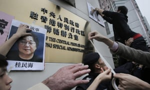 Protesters try to stick photos of missing booksellers, one of which shows Gui Minhai at left, during a protest outside the Liaison of the Central People's Government in Hong Kong.