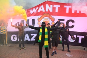 Fans stand in front of a 'We Want The Glazers Out' banner.