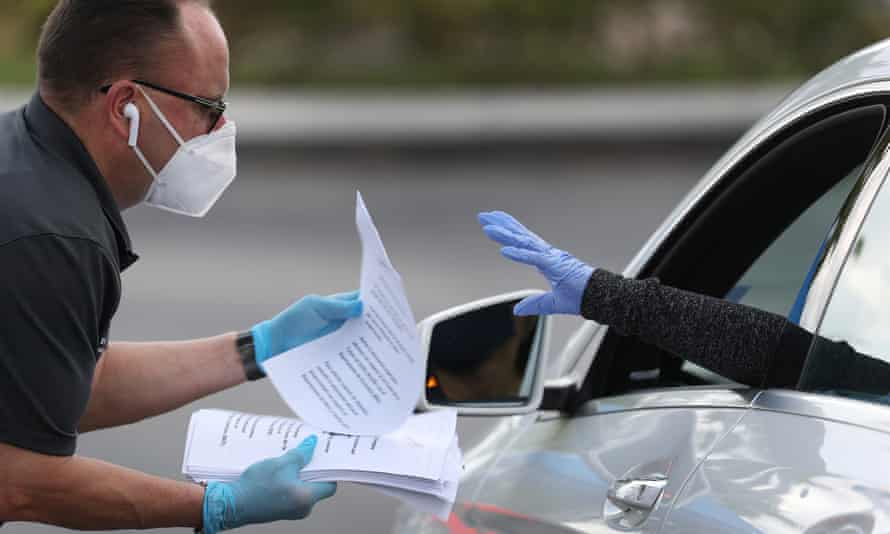 A worker for the town of Hialeah, Florida, hands out unemployment applications to people in their vehicles.