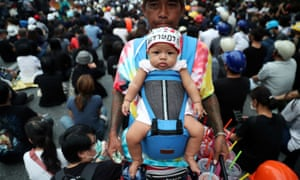 A vendor carrying a baby sells cool drinks to protesters in Bangkok, Thailand