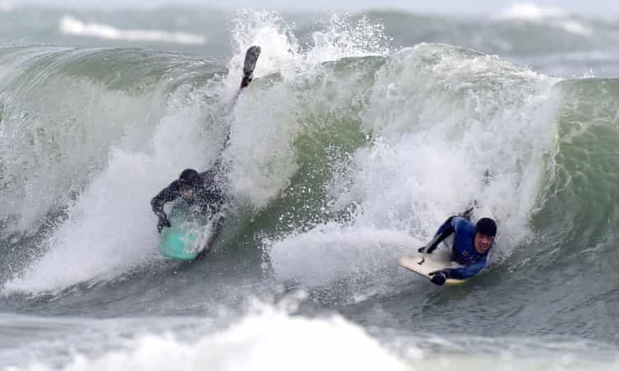 Bodyboarders ride the stormy waves at Broad Haven, Pembrokeshire.