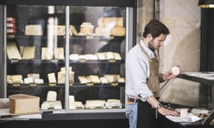 In the Batignolles, the fromagerie Formaticus has a loyal following for its cheeses and sharing platters. In this image a shopworkers wraps cheese for a customer.