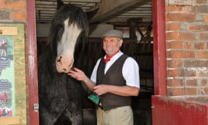 A man, dressed in 1940s attire, petting a horse at Tatton Park Farm, Cheshire.
