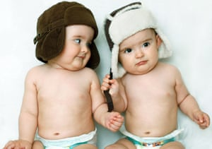 Twin baby boys wearing ear-flap winter hats and nappies