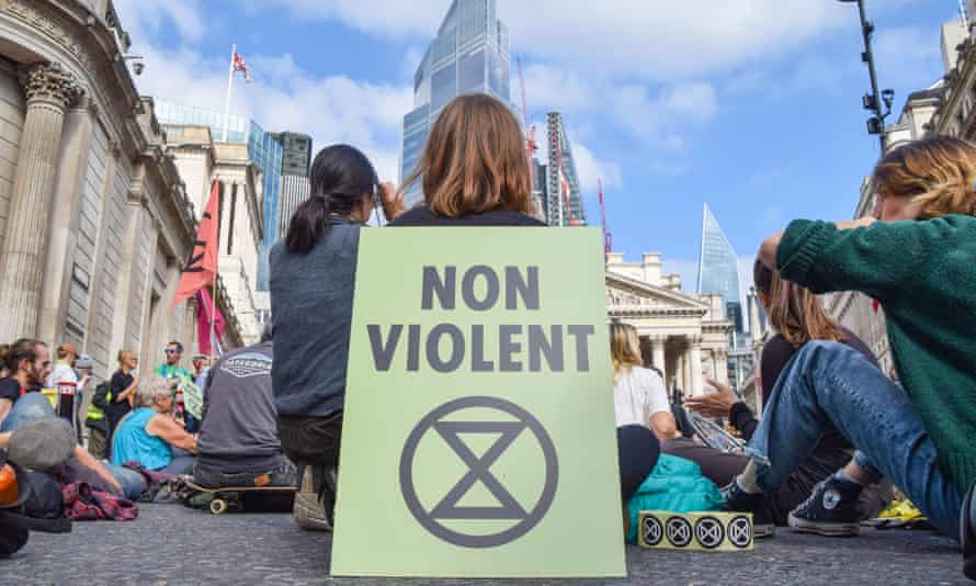 A 'Non-Violent' placard with an Extinction Rebellion symbol is seen during the demonstration outside the Bank of England.