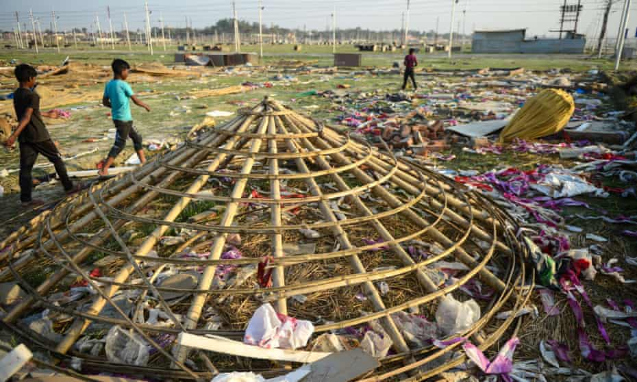 Indian villagers search for reusable materials at a religious camp after the end of Kumbh Mela.