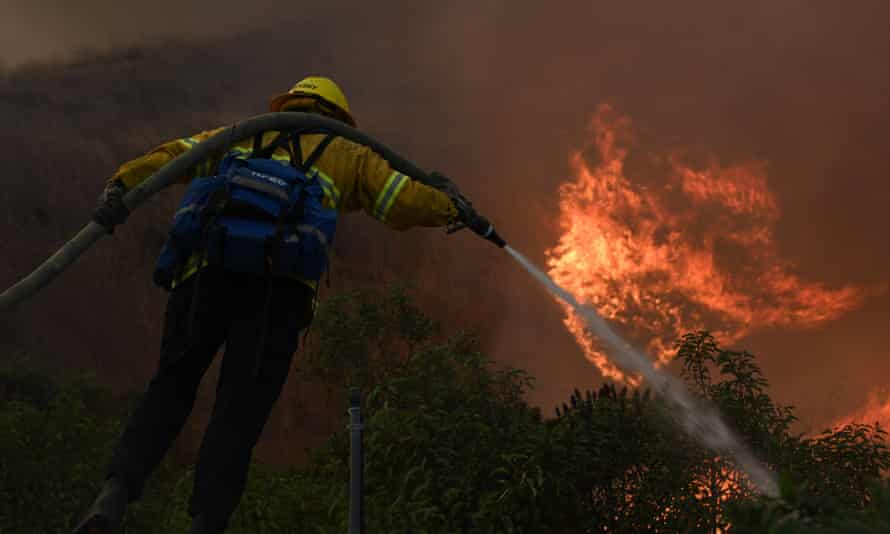 firefighter sprays the flames of a wildfire in California.