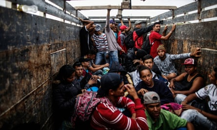 Venezuelan migrants travel aboard a truck in Tumbes, Peru, near the Ecuador border, on 1 November.
