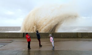 A family brave strong winds as waves crash over the tidal wall on New Brighton Promenade