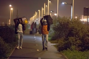 """Refugees who are staying in France make their way to the hanger before daylight from the """"Jungle"""" where authorities are processing them before sending them to different parts of France."""