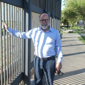 Michael Seifert, a former priest and now migrants' advocate, at the border fence he crosses regularly for this work, between Brownsville and Matamoros.