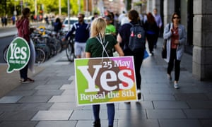 A woman carries a placard urging voters to back the liberalisation of abortion laws in Ireland.