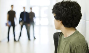 A schoolboy looks nervously at bullies