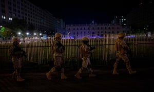 Soldiers patrol the presidential government palace during curfew in Santiago on Monday night.