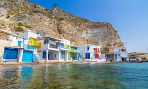 colourful houses under cliff with clear sea in front