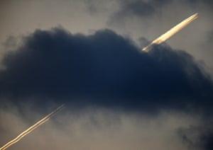 An aircraft flies over Frankfurt, leaving contrails above the cloud