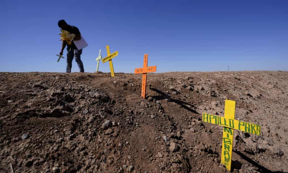 Hugo Castro leaves crosses at the scene of a fatal accident in Holtville, California.