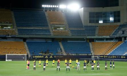 Cádiz and Oaasuna players hold a minute's silence at the empty Carranza stadium.