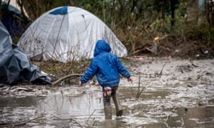 A refugee child walks in the mud in refugee camp near Dunkirk, northern France.