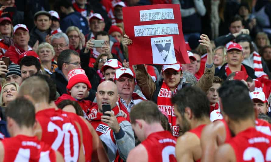 A Sydney Swans supporter holds an' I Stand with Adam' banner in 2015 after Goodes was criticised for fighting back over the abuse he received.