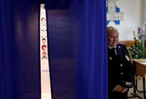 A police officer stands guard near a voting booth at a polling station in Moscow.
