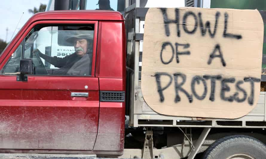 a farmer drives by with a 'howl of a protest' sign in new zealand